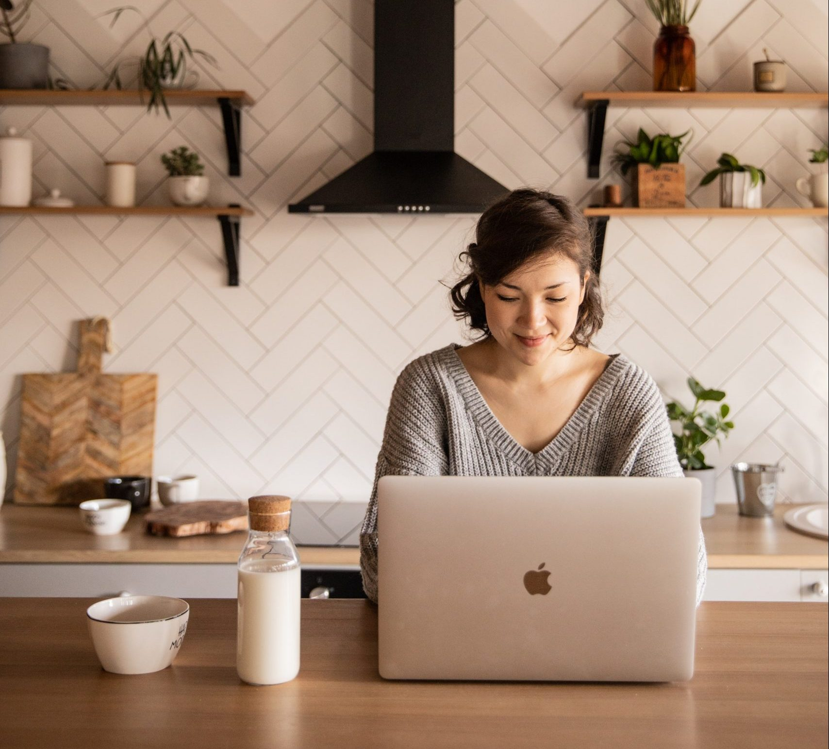 Woman shopping on laptop in contemporary kitchen
