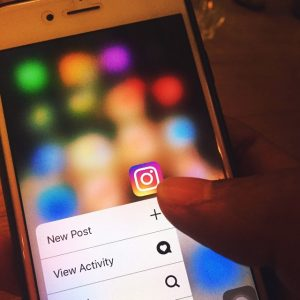 Close up photo of thumb on Instagram icon on smartphone